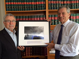 """Mark Gibson (left) receives a photograph from Samuel L. """"Tony"""" Milbank, Chair of the Board of the Milbank Memorial Fund, (right), in celebration of his retirement."""