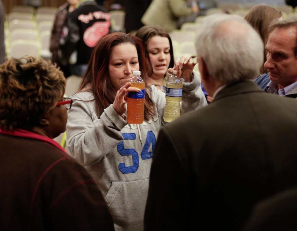 LeeAnne Walters of Flint, Michigan, shows water samples from her home from January 21, 2015 and January 15, 2015 to Flint's emergency manager Jerry Ambrose after city and state officials spoke during a forum discussing growing health concerns being raised by Flint residents at the Flint City Hall dome on January 21, 2015. (Credit Image: © Ryan Garza/Detroit Free Press via ZUMA Wire)